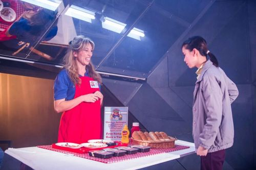 Liz (Daisy Haggard) explains to Junhee (Katie Leung) the system for buying a hot dog