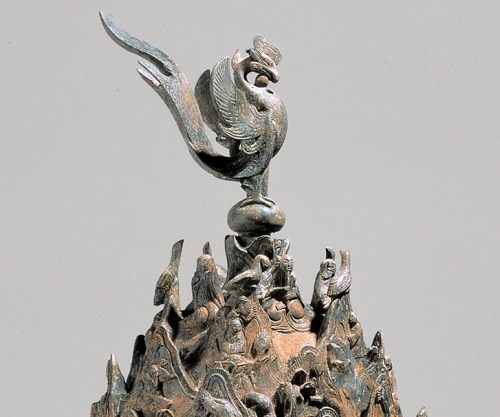 The phoenix on top of the incense burner.