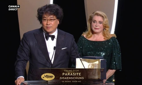 Bong Joon-ho accepts the award from Catherine Deneuve