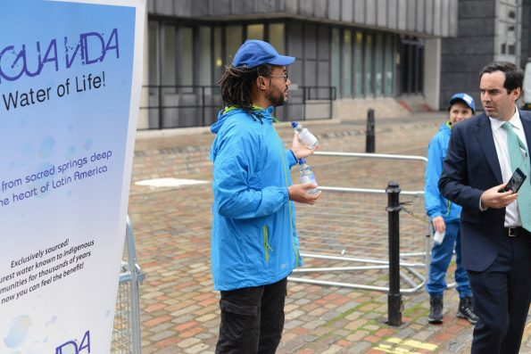 Three Penny Festival actors giving out free water to wary shareholders outside BHP's AGM