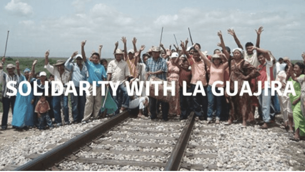 Description: a crowd of people from the communities of La Guajira, Colombia stand across a railway track, waving at the camera. Text across the image reads: SOLIDARITY WITH LA GUAJIRA.