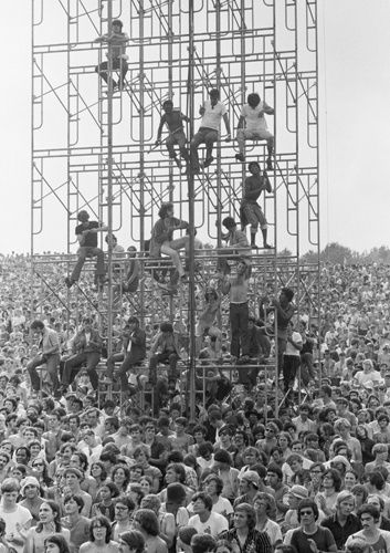 Members of the audience climb the sound tower to secure a better view at the Woodstock Music & Art Fair, Bethel, NY, August 15, 1969. © Iconic Images/Baron Wolman