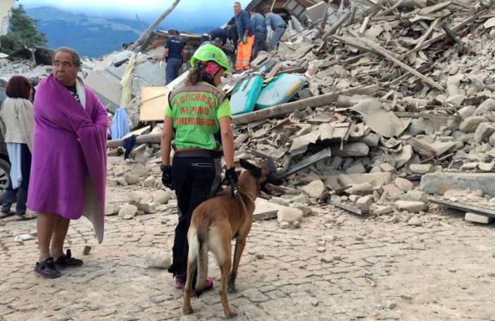 A man wrapped in a blanket looks on as a rescuer with a dog stand in front a collapsed house following a quake in Amatrice, central Italy, August 24, 2016. REUTERS/Emiliano Grillotti