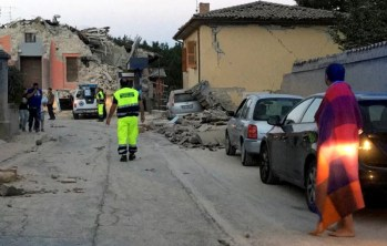 People stand along a road following a quake in Amatrice, central Italy, August 24, 2016. REUTERS/Emiliano Grillotti