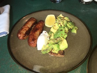 Avocado on toasted rye bread with lemon, chilli, poached egg - extra two sausage
