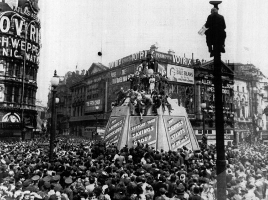 People jam London's Piccadilly Circus during celebration of V-E Day May 8, 1945. Some perch atop Eros Statue and one person has climbed a post.