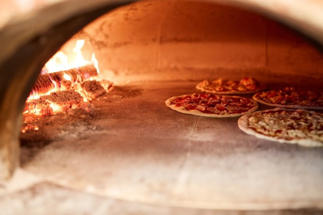 pizza baking in oven at pizzeria