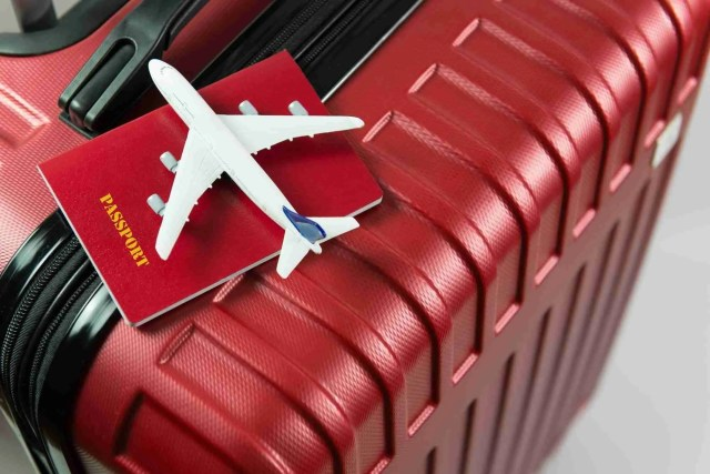 Red passport and airplane model on red luggage