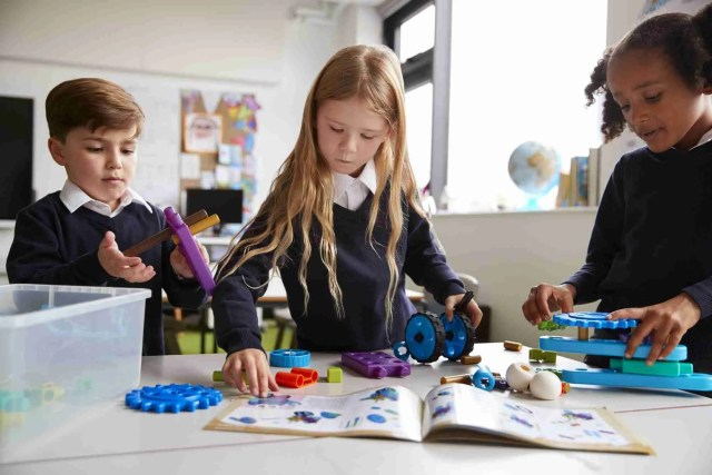 Three primary school children following an instruction book and using construction blocks