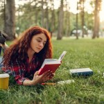 Female student with cup of coffee lying on grass