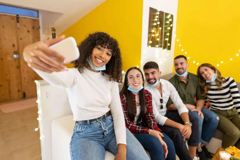 Group of young people at home wearing lowered protective medical mask posing for selfie sitting on a couch at home party, Afro american girl using smartphone to share on social network happy moments