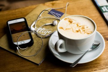 Photo of a smartphone, Apple earphones, and a cup of coffee