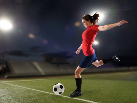 Young woman playing soccer insie a stadium at night