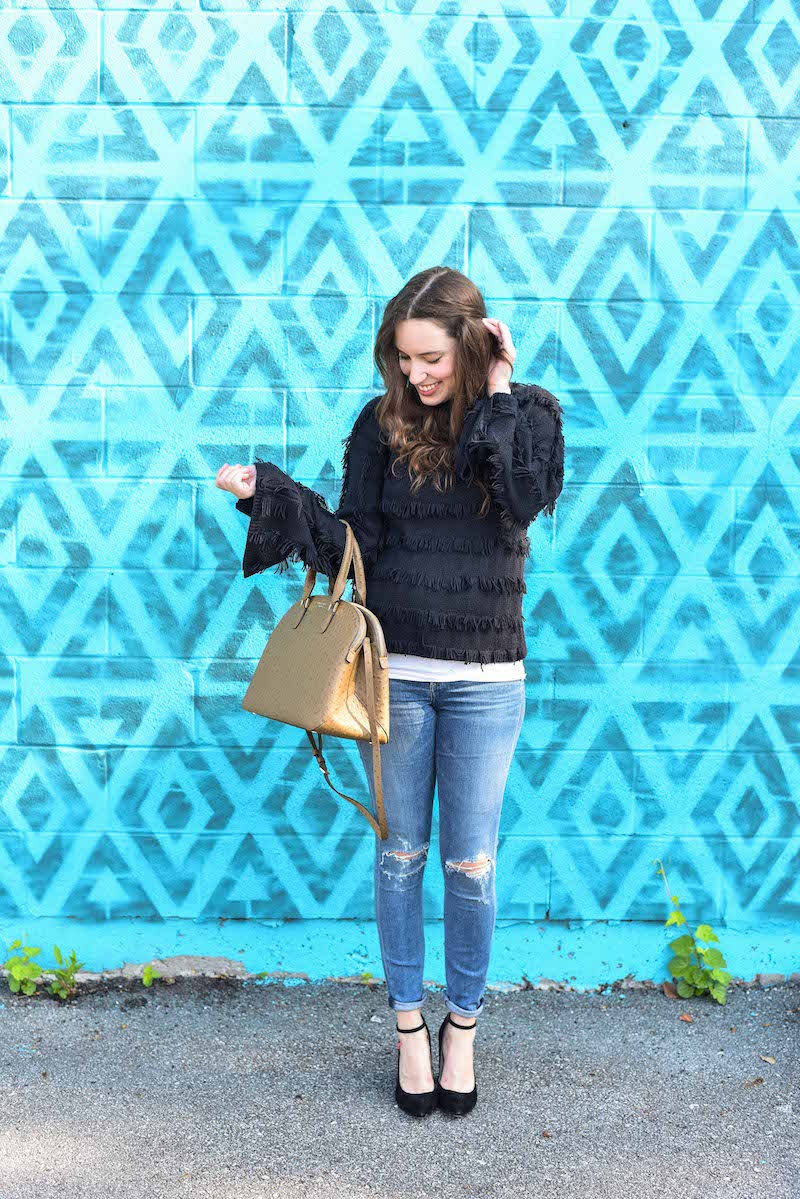 Houston Fashion Blogger Lone Star Looking Glass styles Yoana Baraschi's black fringed sweater with distressed citizen jeans and Henri Bendel's Ostrich Dome Satchel.
