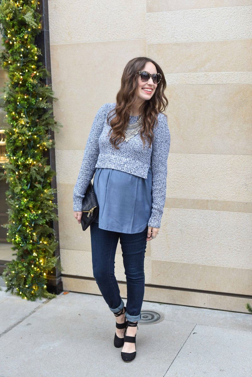 Holiday maternity outfit inspiration in a purple pea in the pod peplum top with skinny jeans and black heels.
