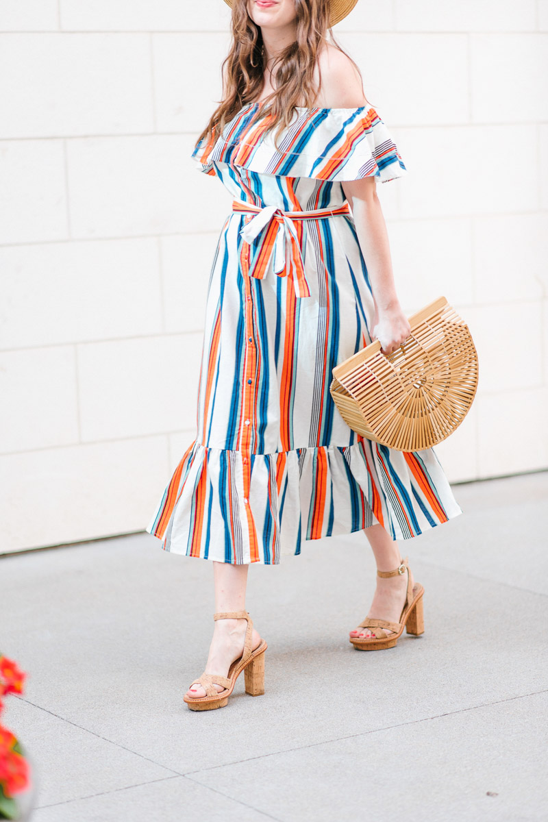 Houston blogger styles a striped moon river off the shoulder dress with a Cult Gaia bag.