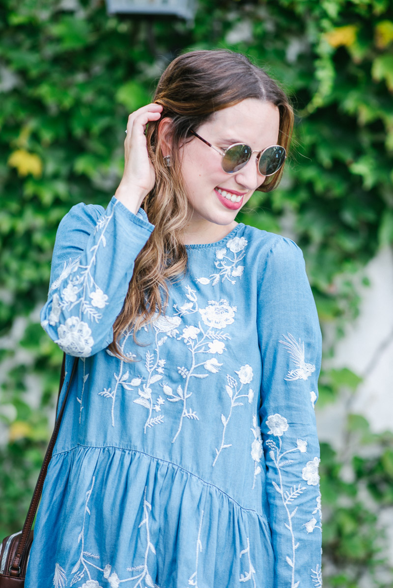 Anthropologie circle sunglasses paired with a blue and white embroidered sundress.
