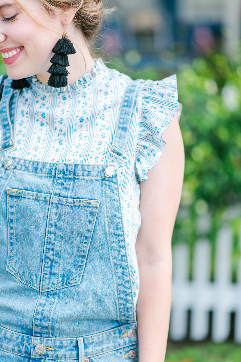 A ruffle sleeve top with distressed overalls.