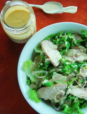 Grilled chicken caesar salad in a bowl next to a jar of caesar salad dressing.
