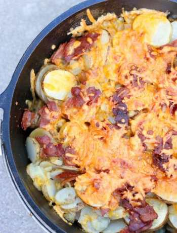 Cooked dutch oven potatoes with cheese and bacon on top.