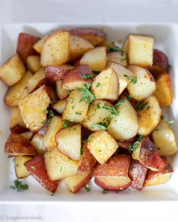 Crispy roasted potatoes on square plate.
