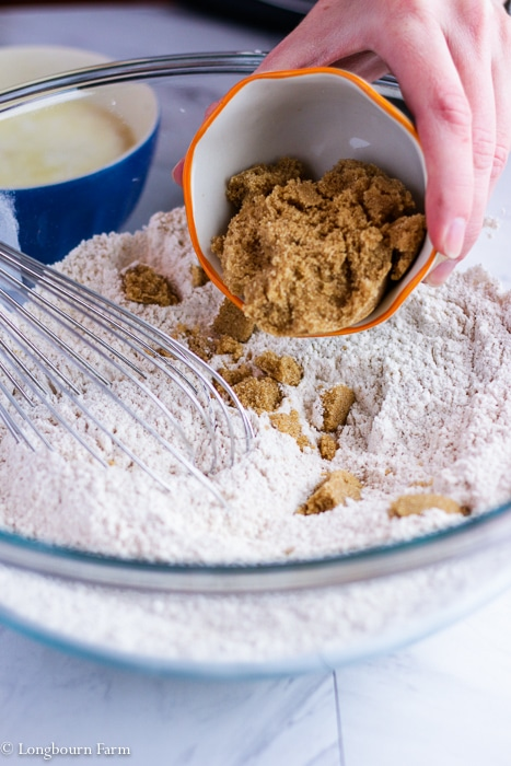 Pouring brown sugar into the dry ingredients.