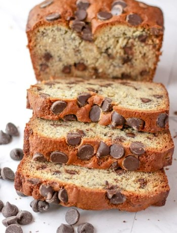 Three slices of chocolate chip banana bread lying down in front of the loaf of chocolate chip banana bread.