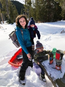 Alli standing with her two kids near a snowy picnic bench.