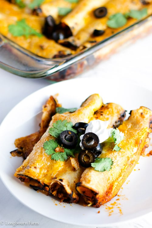 Three beef enchiladas on a white plate with a pan of beef enchiladas in the background.