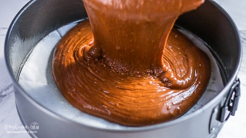 Pouring basic chocolate cake recipe batter into a springform pan lined with parchment paper.