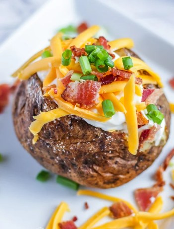 Side, front view of a baked potato loaded with sour cream, cheese, bacon, and green onions.