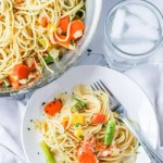 Pasta primavera recipe on a white plate next to a glass of water and the pan of pasta primavera.