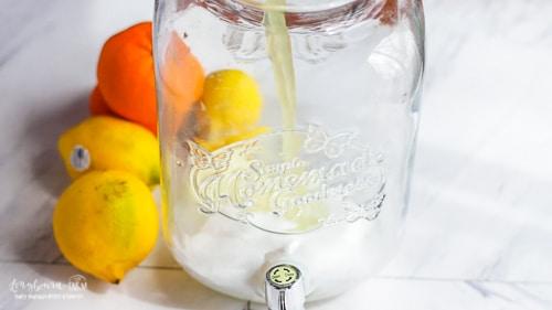 Pouring lemon juice into mixing vat for citrus lemonade.
