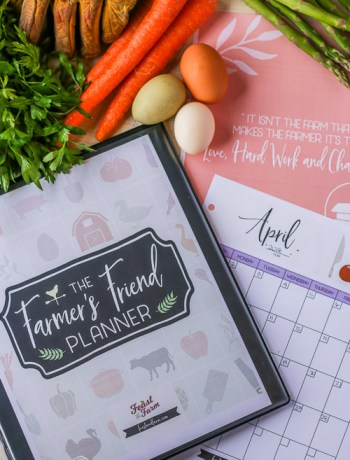 Assembled Farmer's Friend farm planner with sheets out next to it with eggs, gloves, and produce surrounding the farm planner.