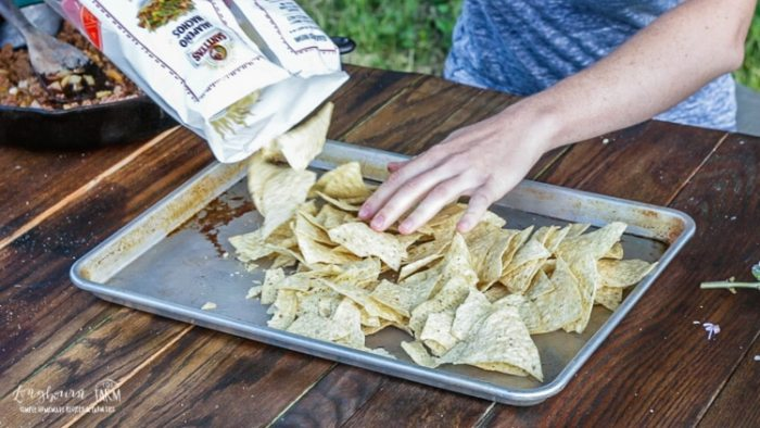 Spreading tortilla chips on the sheet tray for ground beef nachos.