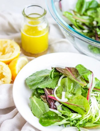 Easy green salad on a white plate next to the salad bowl, lemons and lemon vinaigrette.
