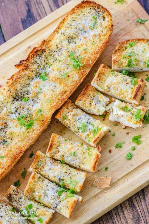 Cheesy garlic bread recipe cut up on a cutting board.
