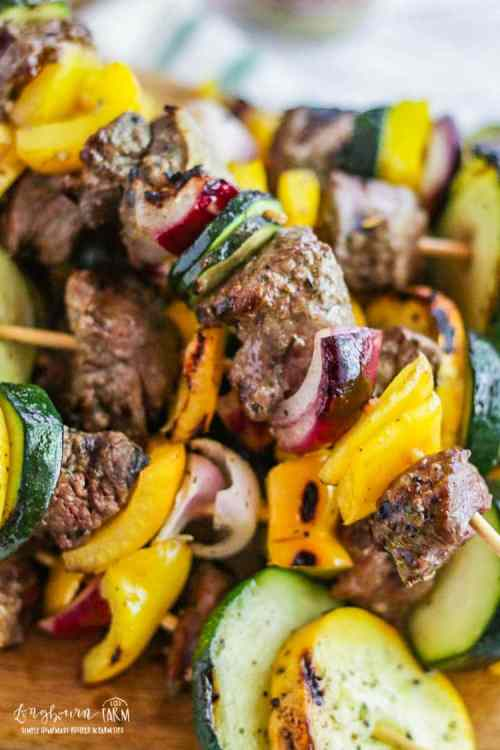 Close-up of finished steak kabobs on a wooden board.