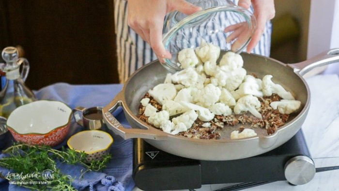 Adding cauliflower to the GRIZZLY cast iron pan.