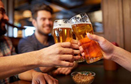 people, men, leisure, friendship and celebration concept - happy male friends drinking beer and clinking glasses at bar or pub - Longmeadow Bachelor Party