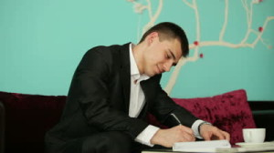 stock-footage-young-guy-writing-something-and-thinking-with-a-smile
