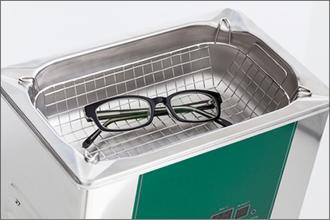 Eine Brille liegt zur Reinigung im Ultraschallbad