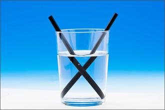 2 schwarze Strohhalme, die in einem Wasserglas vom Licht gebrochen werden