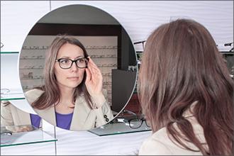 Frau probiert Brillen vor Spiegel an