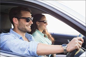 Mann und Frau tragen getönte Brillen beim Autofahren