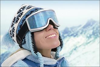 Frau mit Skibrille blickt in die Sonne