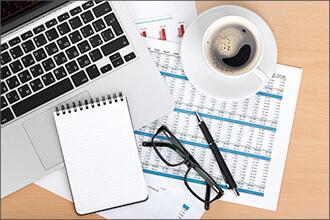 Schreibtisch mit Block, Brille, Stift und Kaffee