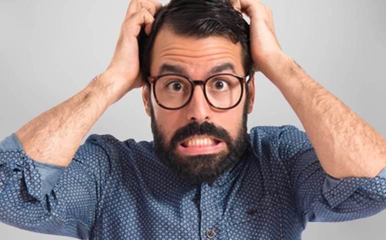 Mann mit Brille rauft sich die Haare