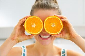 Frau hält sich zwei Orangen vor die Augen