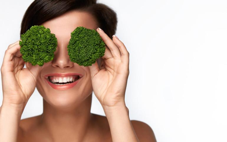 Frau hält sich Brokkoli vor die Augen